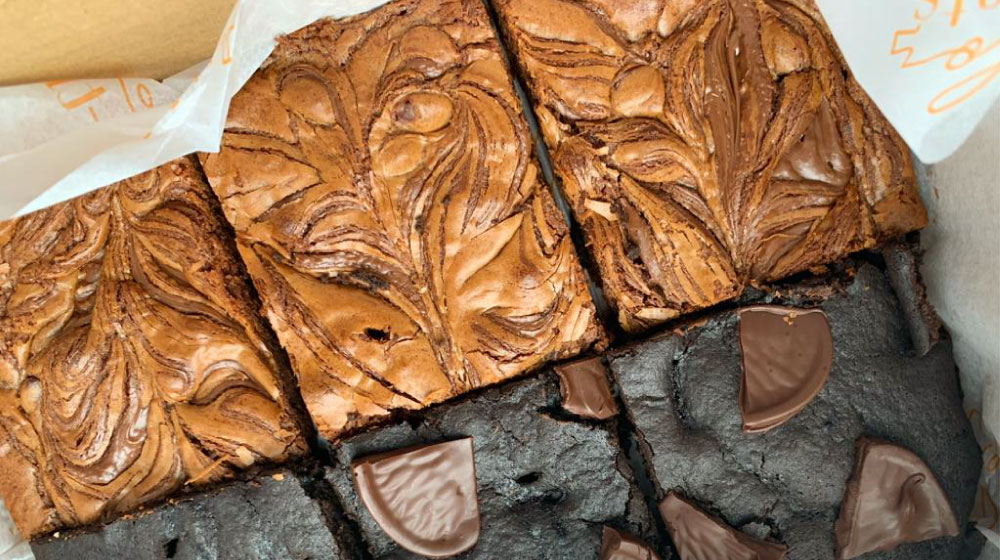 close up shot of 6 brownies in a box