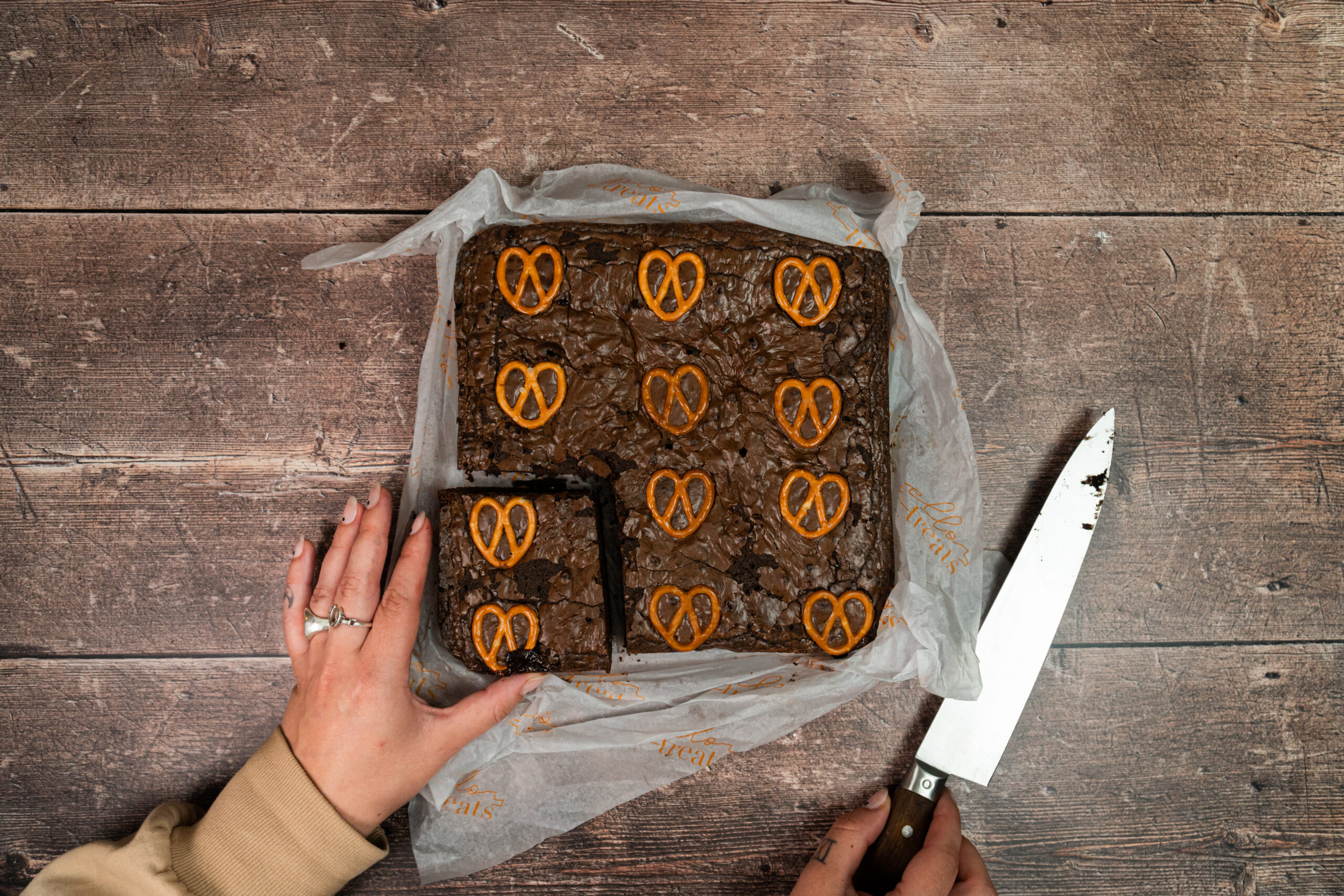 slab of chocolate brownie being cut, topped with pretzel pieces