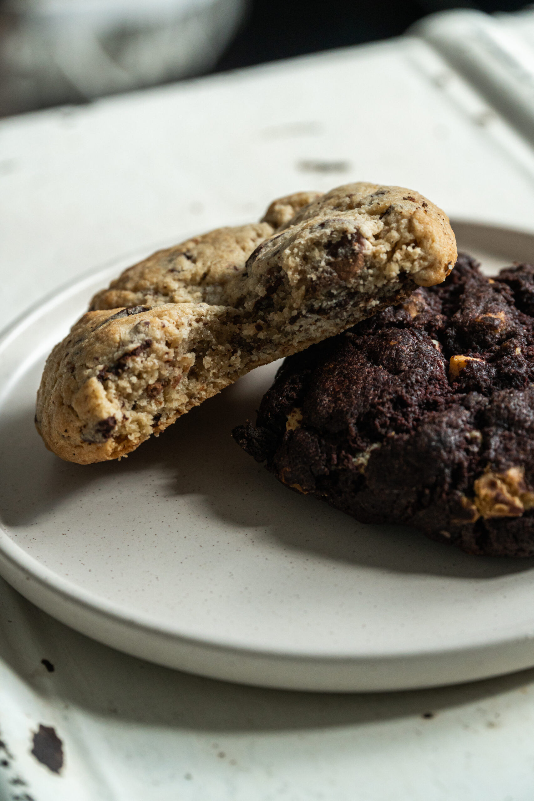2 chunky nyc cookies on a plate, one has a bite taken out of it