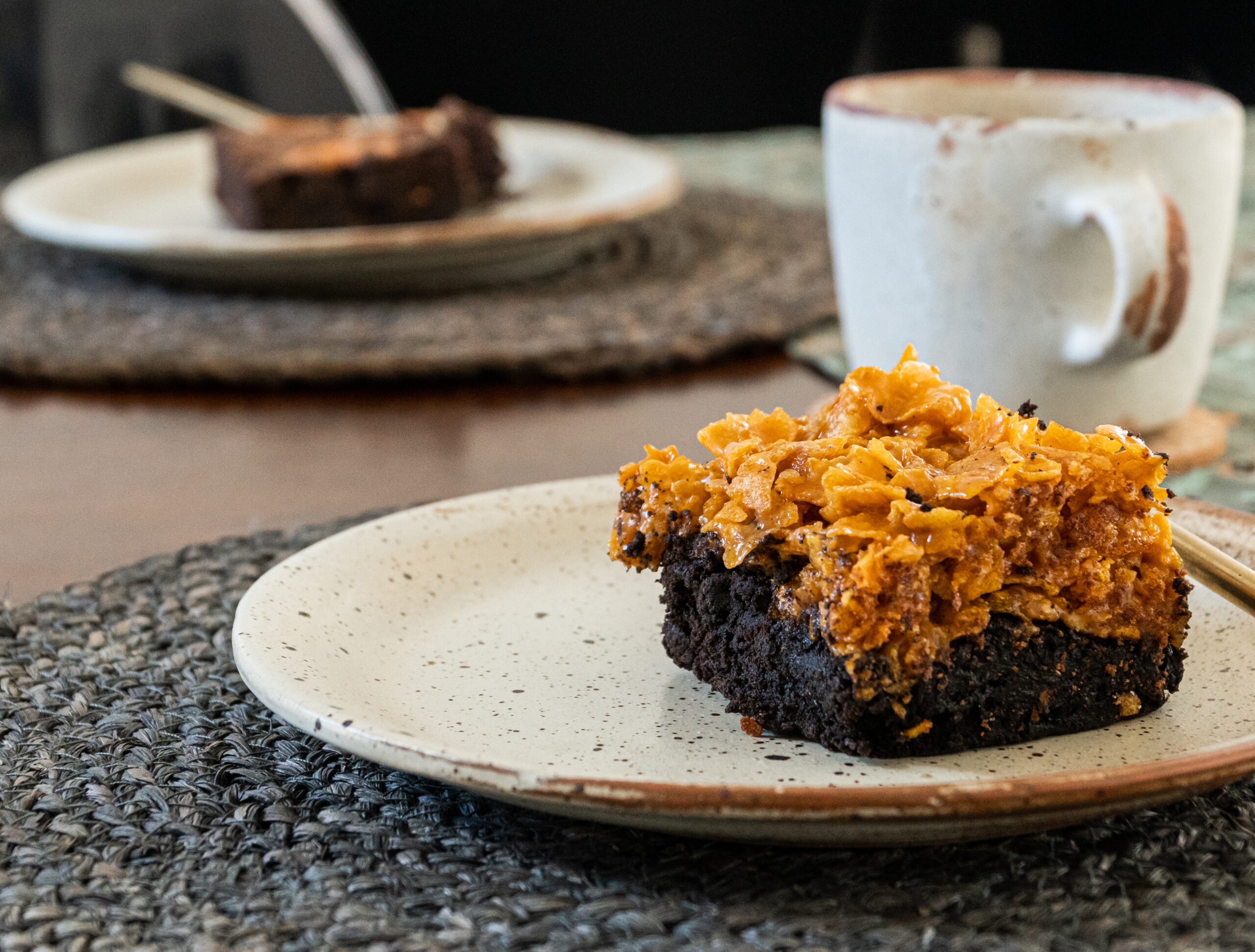 cornflake loaded brownie on a plate with a cup of coffee