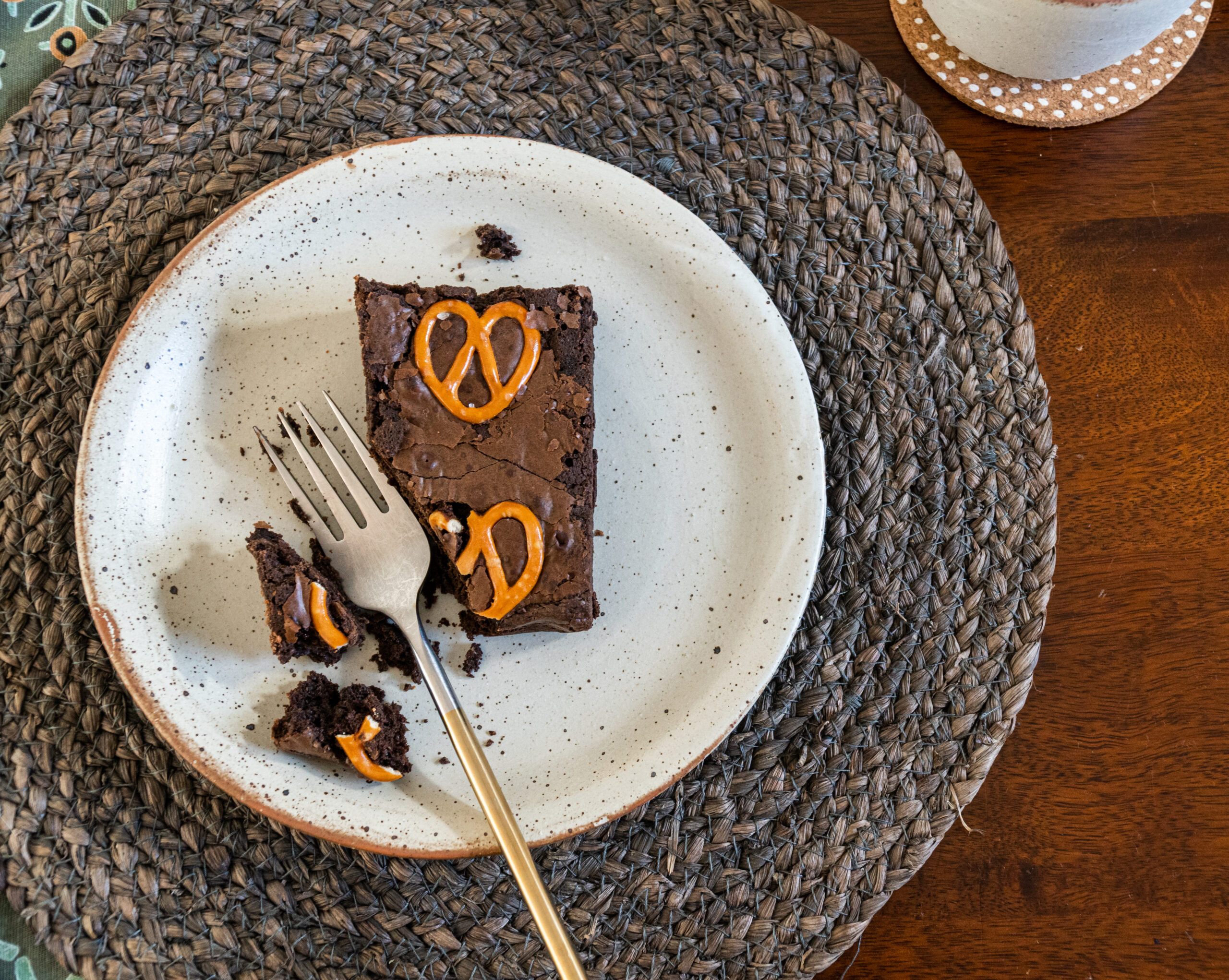 slice of pretzel brownie on a plate with a fork and placemat