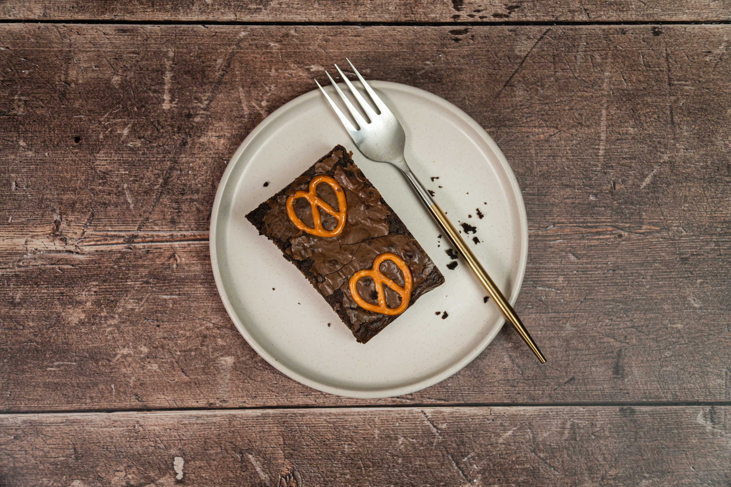 slice of pretzel brownie on a plate with a fork